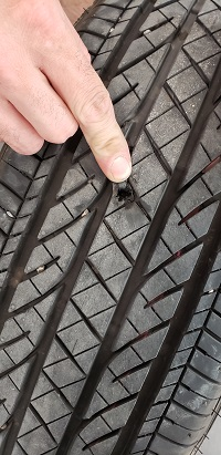finger pointing at hole in tire
