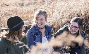 three women smiling in a field