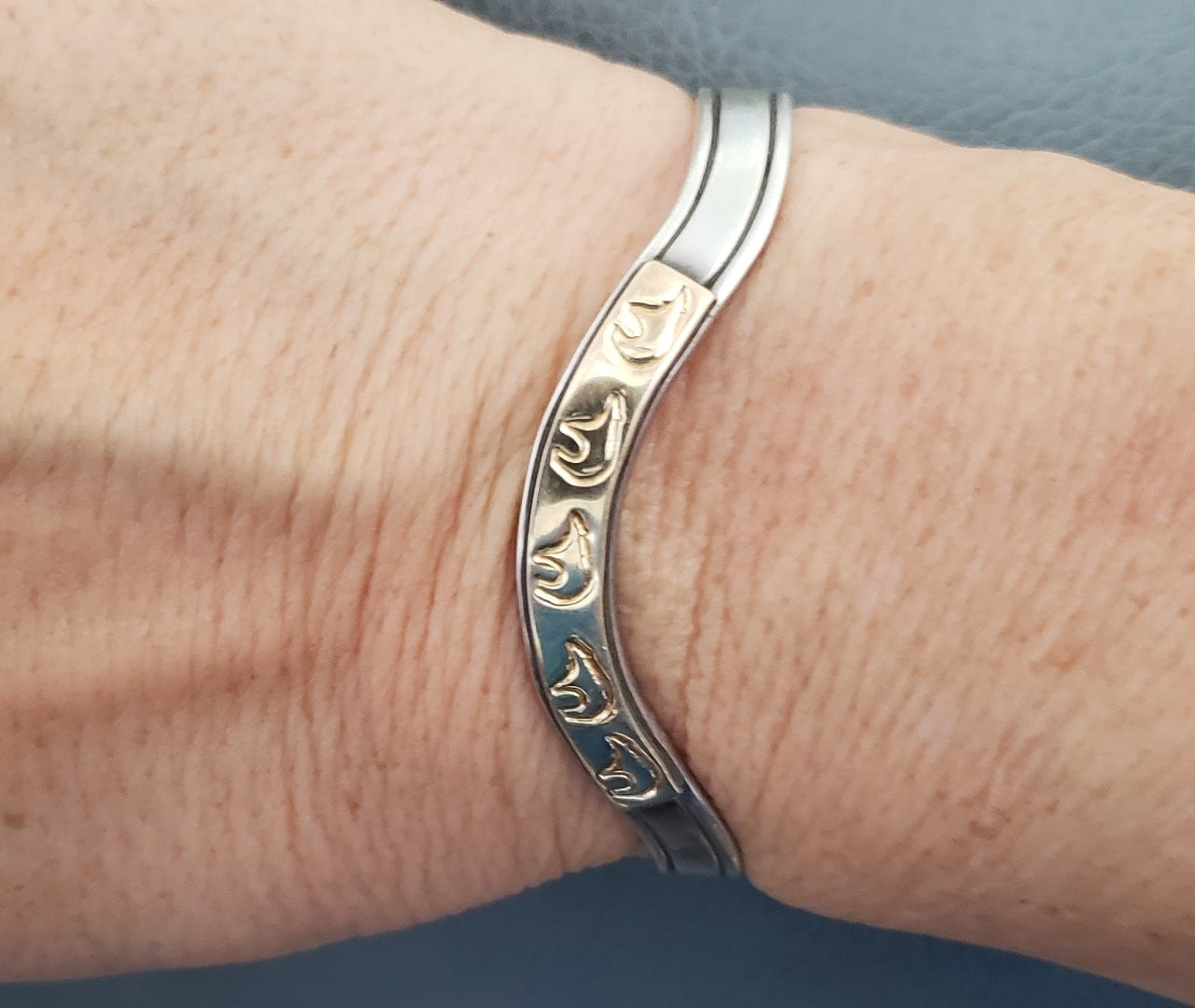 Silver cuff bracelet with gold overlay stamped with bear silhouette