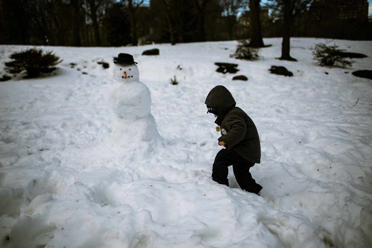 A child playing in the snow with a snowman
