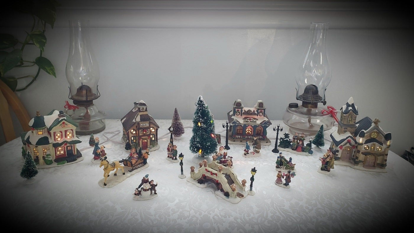 A Christmas village with lighted buildings, various small figures and a lighted Christmas tree in the middle.