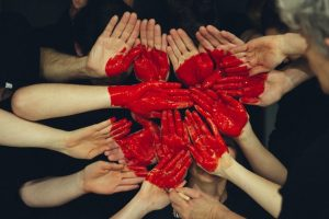Hands crowded together with a red heart painted on them