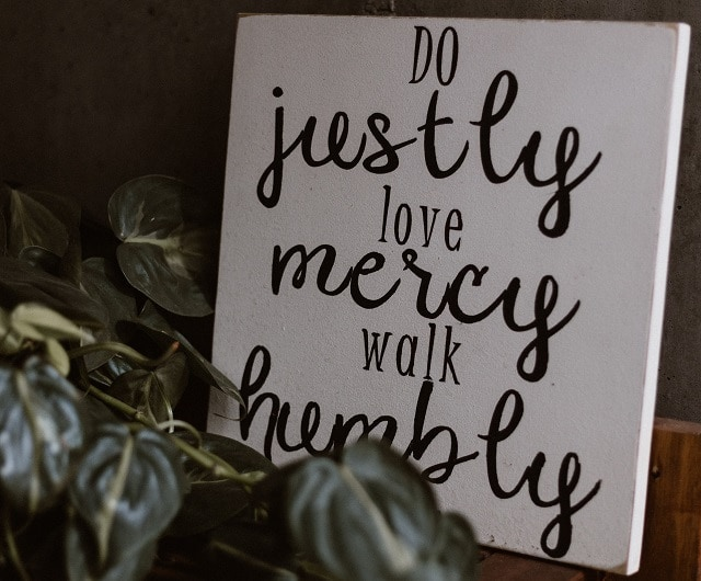 """White sign says in black """"Do Justly, love Mercy, walk Humbly"""" from Micah 6:8"""