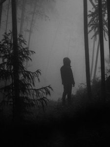 Black and white photo of a person standing in foggy woods