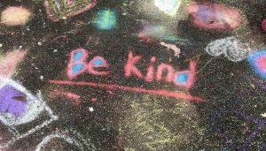 Words on sidewalk say Be Kind in chalk.