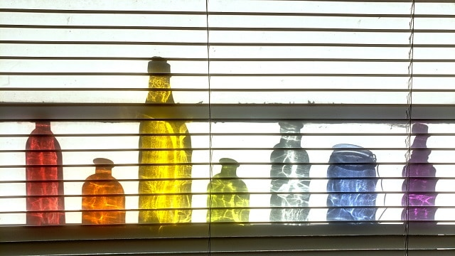 A row of colored bottles in the sun on a windowsill behind translucent blinds