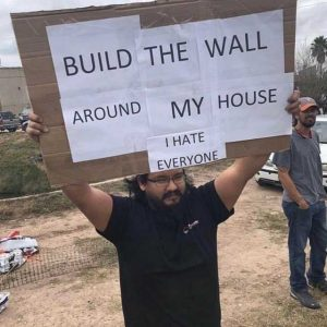 Man holding sign saying to build the wall around his house - he hates everyone