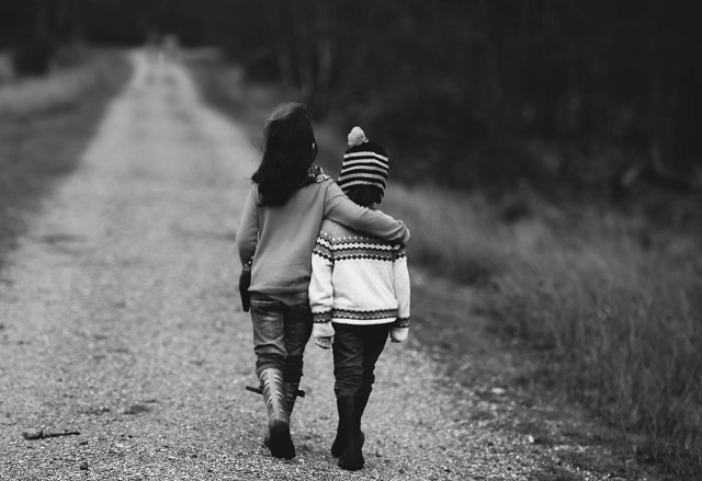 Girl walking with arm around her smaller companion