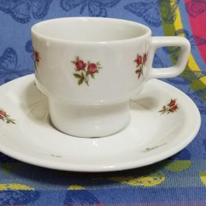 A white cup and saucer with red rosebuds on them