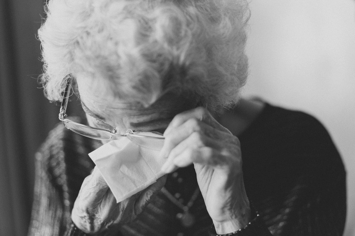 Black and white photo of old woman crying