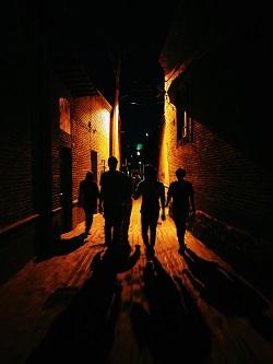 Silhouettes of people walking down dark alley