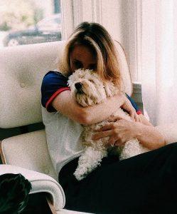 Woman cuddling medium sized dog