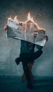 man reading newspaper that's on fire