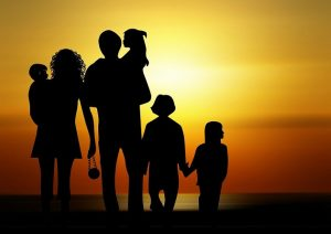 A family silhouetted in front of a sunset