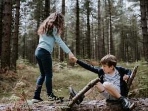 Girl lending hand to help boy get up from the ground