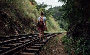 girl with backpack walking away on train tracks