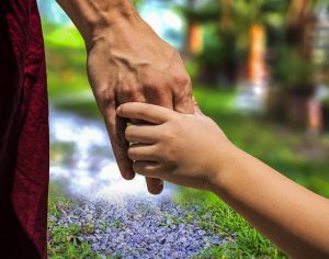 child's hand holding adult's