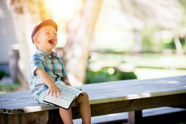 Boy on bench laughing with open Bible on his lap