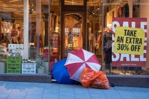 A homeless person camped in front of a clothing store with Sale signs in the window.
