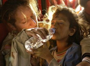 woman in desert camo giving young girl water from a bottle