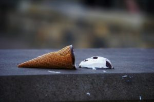 ice dream cone on its side with the ice cream melting next to the cone