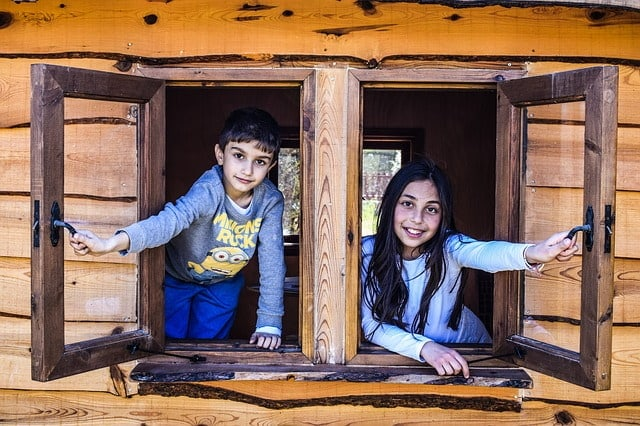 Two kids looking out the open windows of a cabin