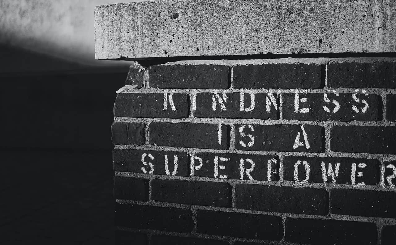 Brick wall with KINDNESS IS A SUPER POWER stenciled on it in white paint