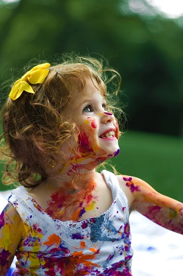 smiling girl with paint all over