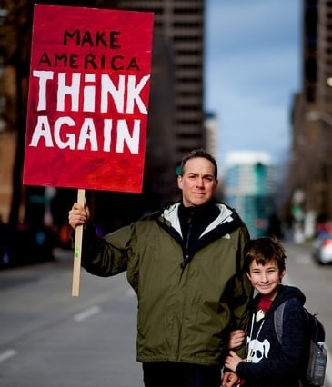 Boy with man holding red sign saying Make America Think Again