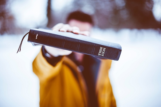 man holding out Bible