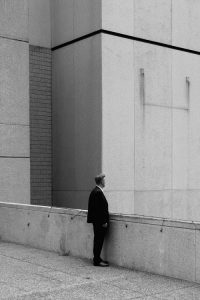 Black and white photo of a man standing among tall concrete buildings