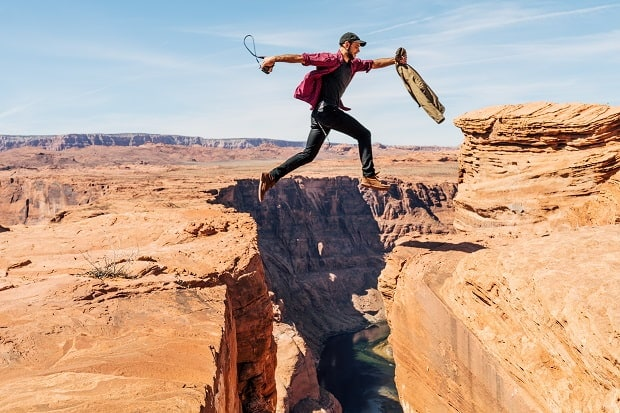 man leaping a gap over a canyon