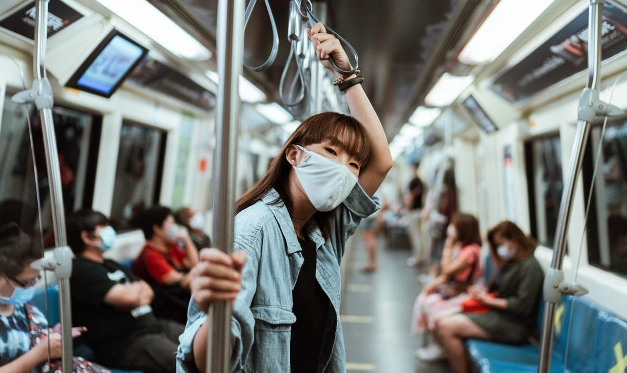 Photo of a woman wearing a medical mask while standing inside a train.