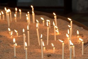 Many lit candles in a tray of sand