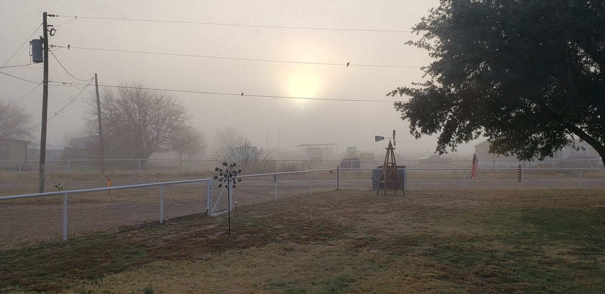 Photo of foggy sunrise in West Texas with small windmill in foreground