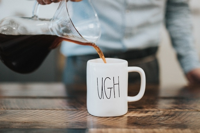 coffee being poured into mug that says UGH