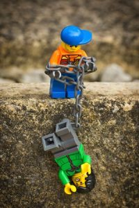 LEGO man rescuing another with chain