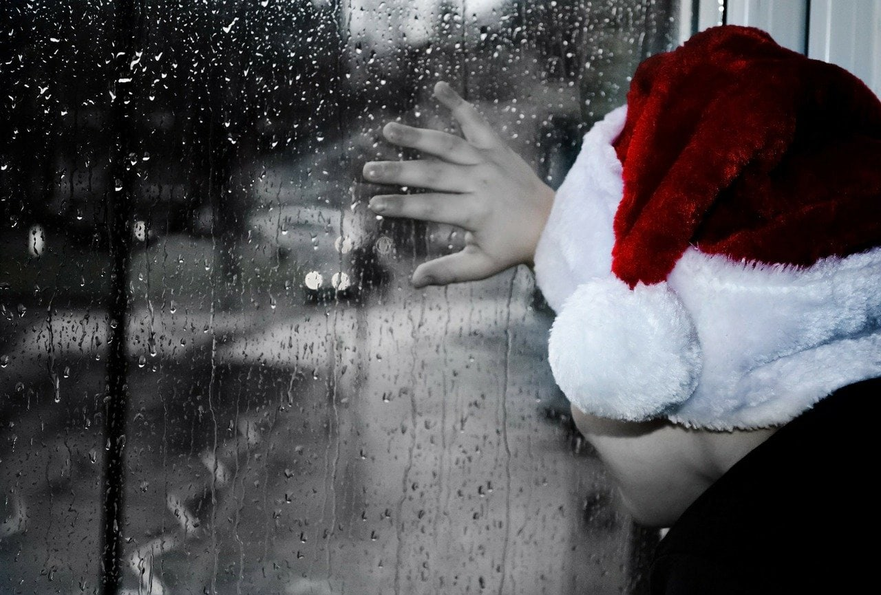 child in a Santa hat looking out a rain-streaked window