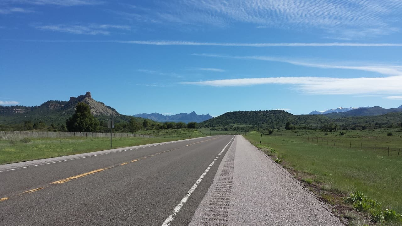 Road stretching into the distance with green hills on one side and mountains on the other.