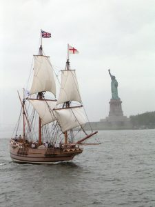 sailing ship in front of the statue of Liberty