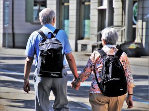 older couple with backpacks holding hands