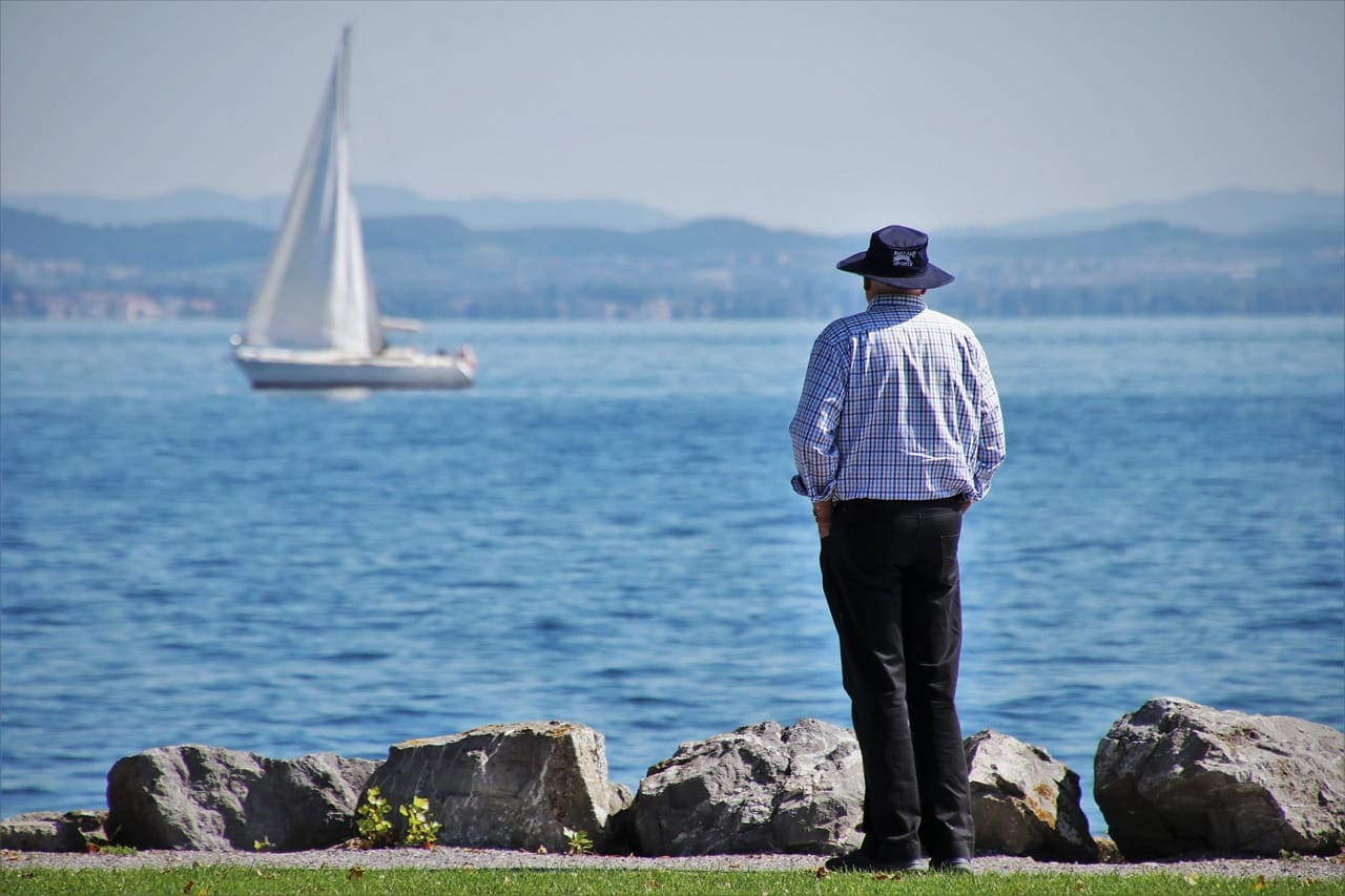 Elderly man standing on shore watching a sailboat go by