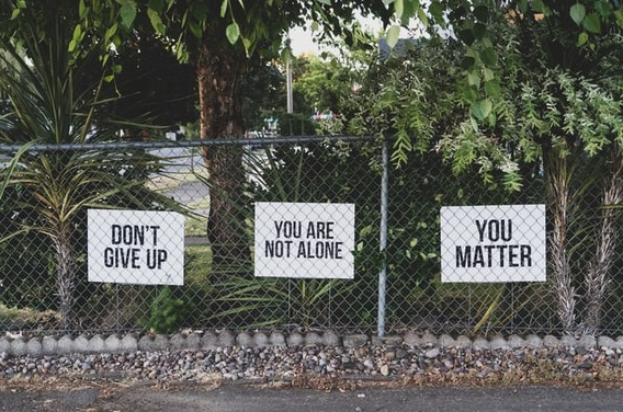 Signs on a fence saying Don't Give Up, You are Not Alone, and You Matter