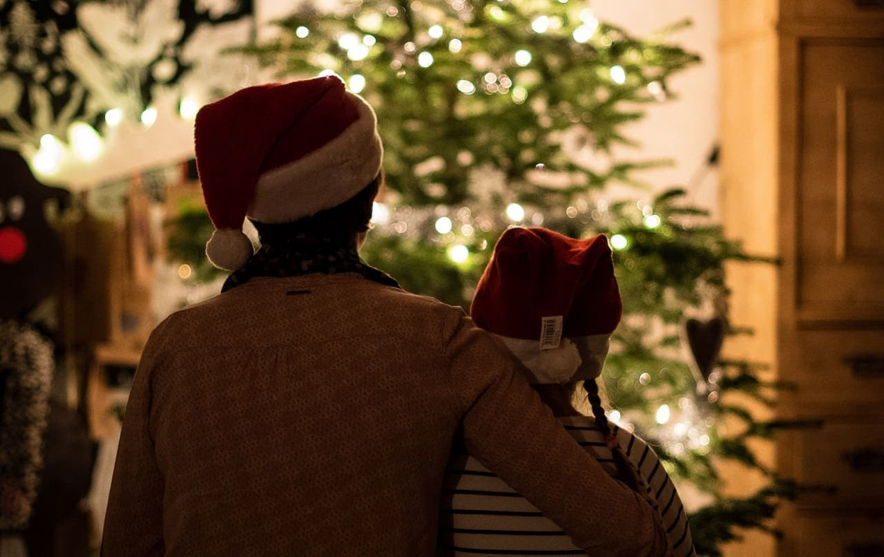 Woman with arm around girl as both wear Santa hats and look at Christmas tree.