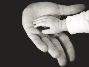 baby's hand resting in an adult's palm