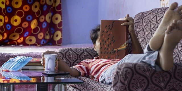 Man lying on couch reading