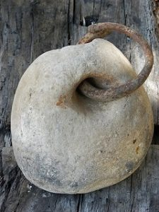 photo of a stone weight with an iron ring through a drilled hole