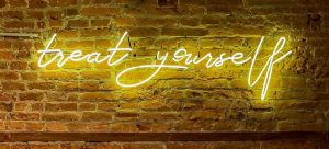 Yellow neon sign that says Treat Yourself