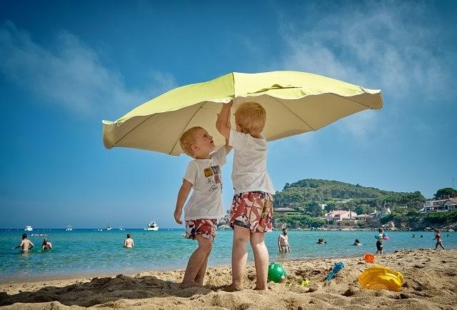 Two boys sharing a sun umbrella