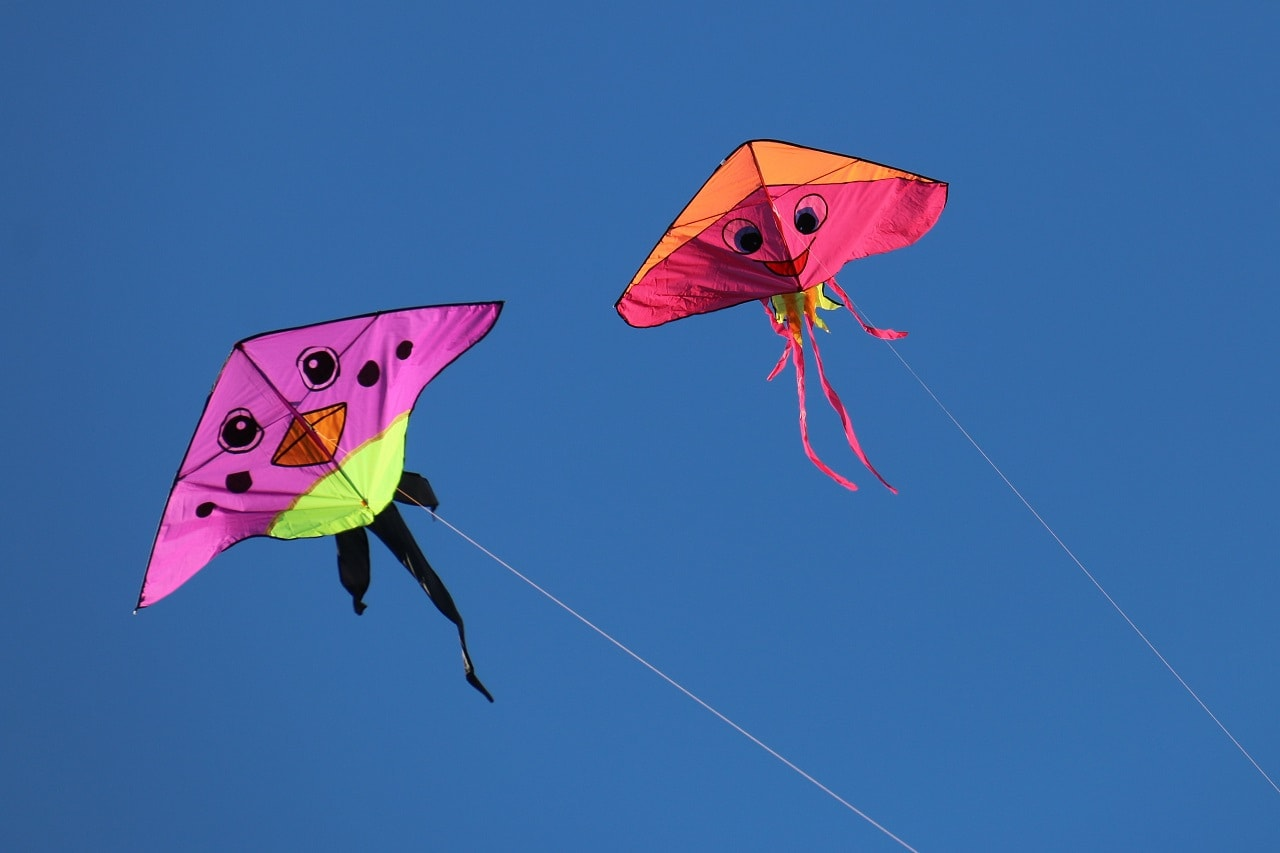 Two triangle-shaped kites with happy faces painted on them flying in the air